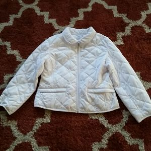 A young girls white puffy jacket.